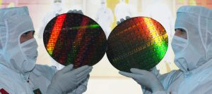 Employees of the unlisted chip manufacturer Globalfoundries show wafers from which chips are made.
