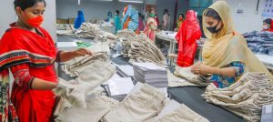 Employees in a clothing factory in Bangladesh sort shorts.  How should German companies control possible grievances there?